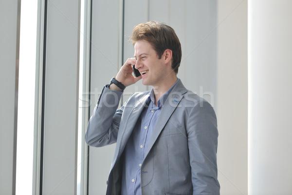 Fiatal üzletember beszéd mobiltelefon fényes ablak Stock fotó © dotshock