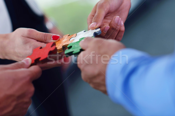 Group of business people assembling jigsaw puzzle Stock fotó © dotshock