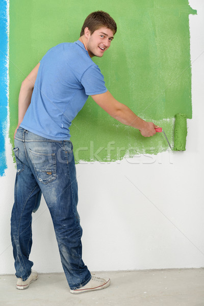 Stock photo: handsome young man paint white wall in color