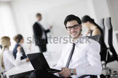 Portrait of a handsome young business man with colleagues in background Stock photo © dotshock