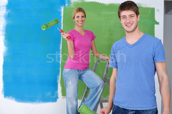 happy couple paint wall at new home Stock photo © dotshock