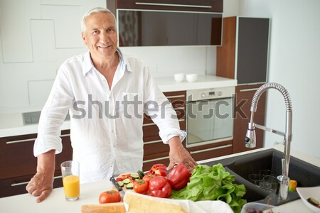 man cooking at home preparing salad in kitchen Stock photo © dotshock