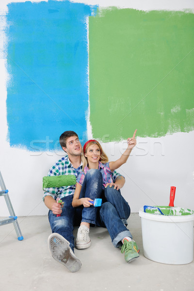 Stock photo: happy young cople relaxing after painting in new home