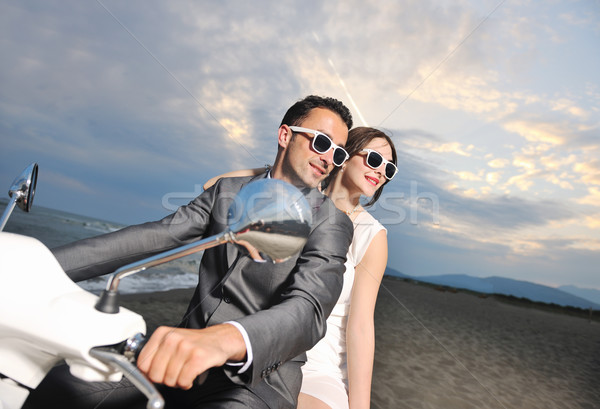 Stock photo: just married couple on the beach ride white scooter
