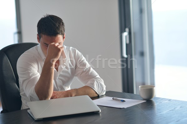 Stock photo: frustrated young business man working on laptop computer at home