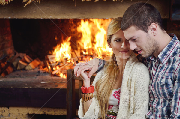 Young romantic couple sitting and relaxing in front of fireplace at home Stock photo © dotshock