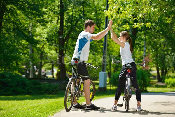 Happy couple riding bicycle outdoors Stock photo © dotshock
