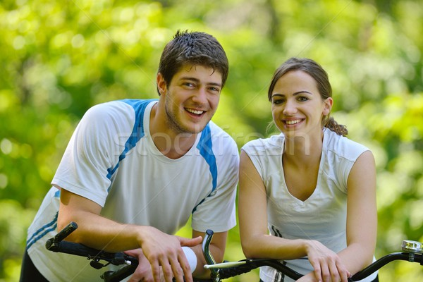 Happy couple riding bicycle outdoors Stock photo © dotshock