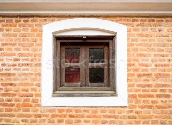 Stock photo: Small wooden window and brick wall