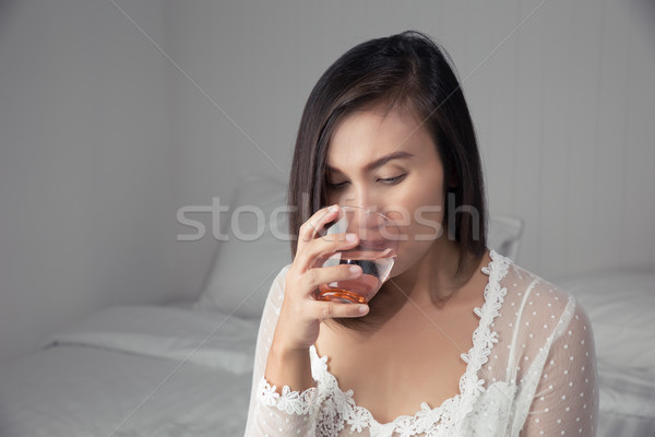 Stock photo: Asian woman in white nightgown drinking water on the bed at bedr