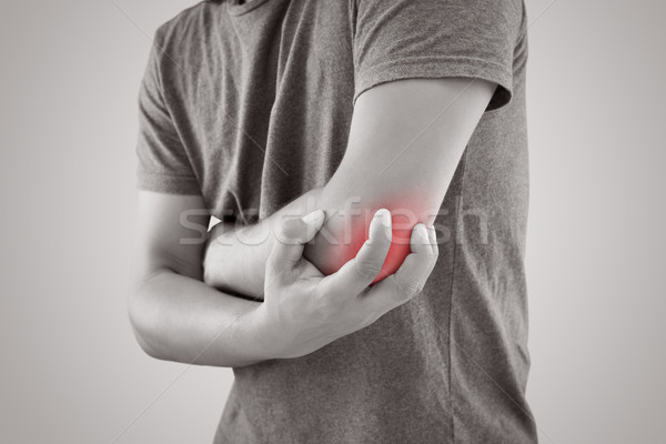 Asian man with pain in elbow against gray background Stock photo © eddows_arunothai