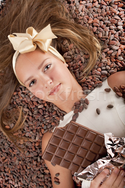 beautiful girl with chocolate on cocoa beans Stock photo © Elegies