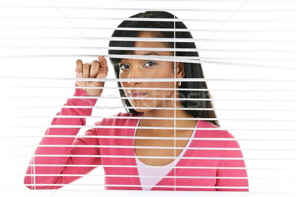 Сток-фото: женщину · глядя · жалюзи · молодые · черную · женщину · горизонтальный