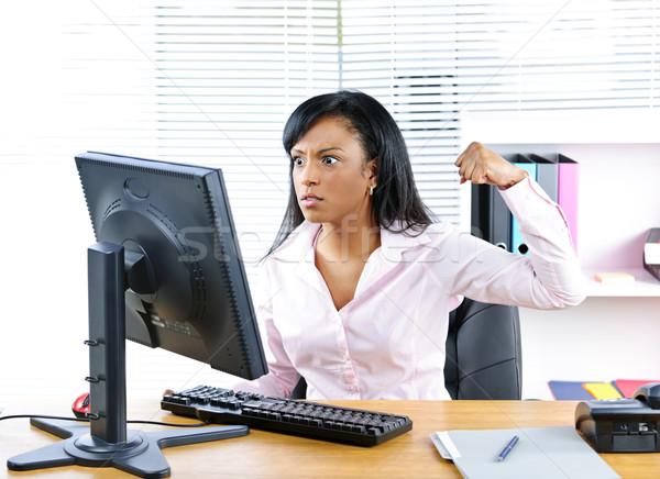 Angry black businesswoman at desk Stock photo © elenaphoto