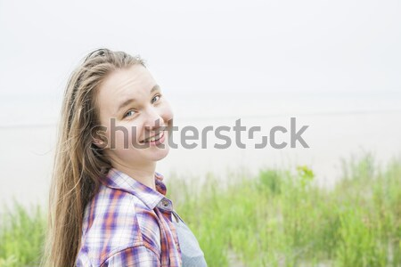 Smiling young woman on beach Stock photo © elenaphoto