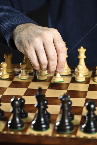 Hand moving pawn on chess board Stock photo © elenaphoto