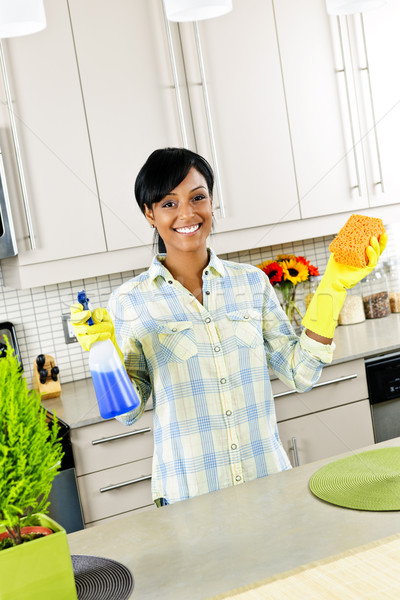 Young woman cleaning kitchen Stock photo © elenaphoto