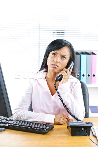 Concerned black businesswoman on phone at desk Stock photo © elenaphoto