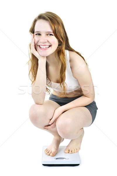 Smiling young girl on bathroom scale Stock photo © elenaphoto