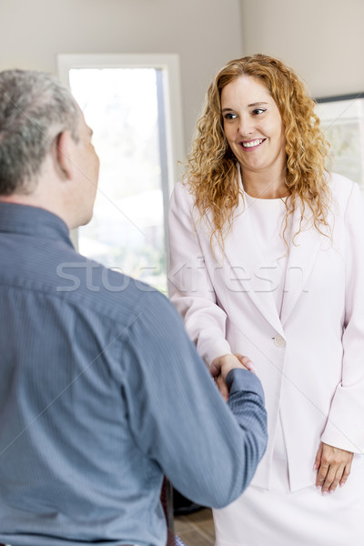 Man and woman shaking hands in office Stock photo © elenaphoto
