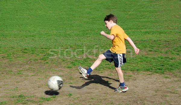 Fiú rúg futballabda fiatal srác futball boldog Stock fotó © elenaphoto