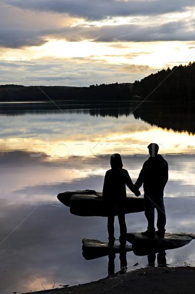 силуэта люди смотрят закат озеро солнце Сток-фото © elenaphoto