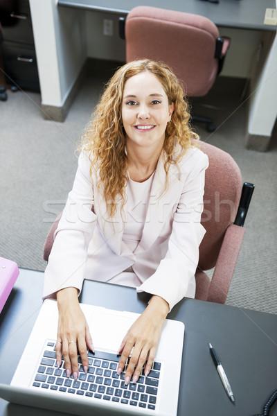 женщину набрав портативного компьютера работу улыбаясь деловая женщина Сток-фото © elenaphoto