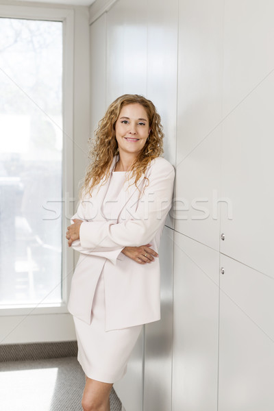 Mujer de negocios pie pasillo sonriendo mujer de negocios oficina Foto stock © elenaphoto