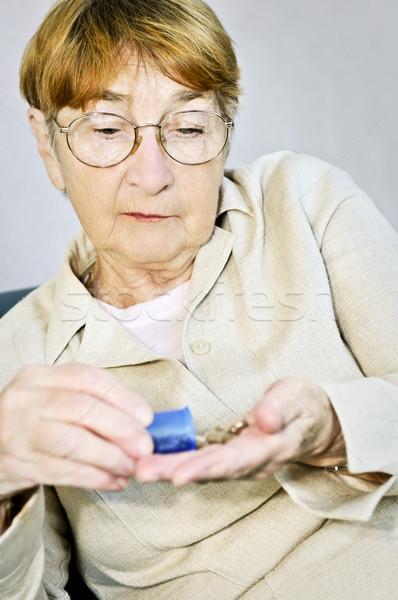 Elderly woman with medication Stock photo © elenaphoto