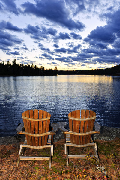 Wooden chairs at sunset on lake shore Stock photo © elenaphoto