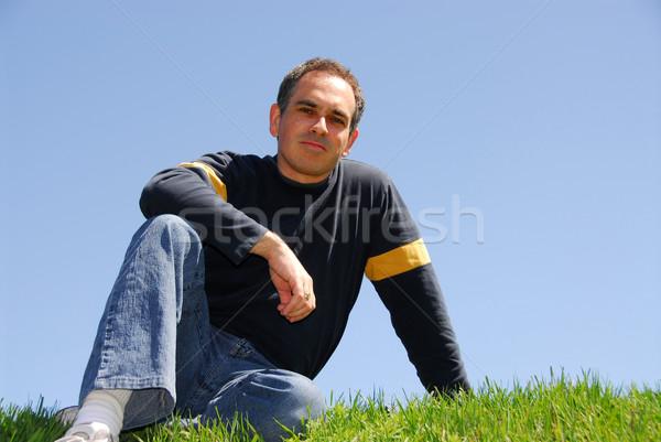 Homem sessão grama sem nuvens céu sorrir Foto stock © elenaphoto
