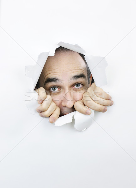 Scared face looking through hole in paper Stock photo © elenaphoto