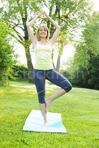 Woman in yoga tree pose Stock photo © elenaphoto
