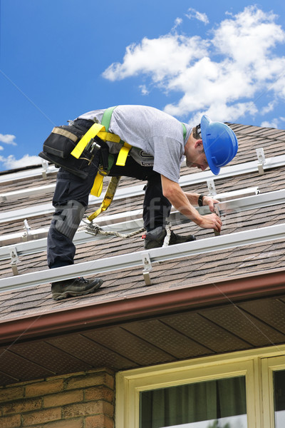 Man working on roof installing rails for solar panels Stock photo © elenaphoto