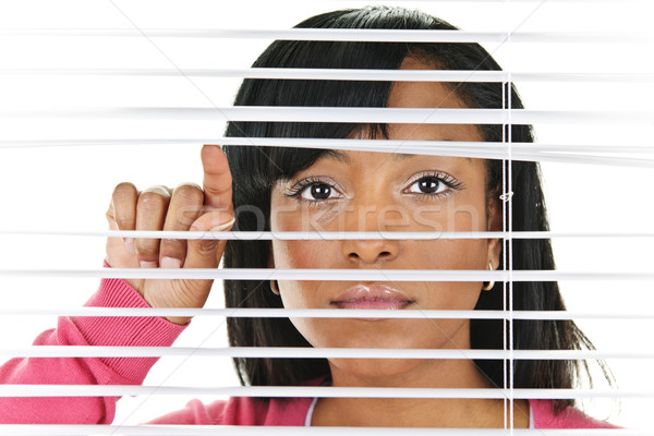 Stock photo: Woman looking through venetian blinds