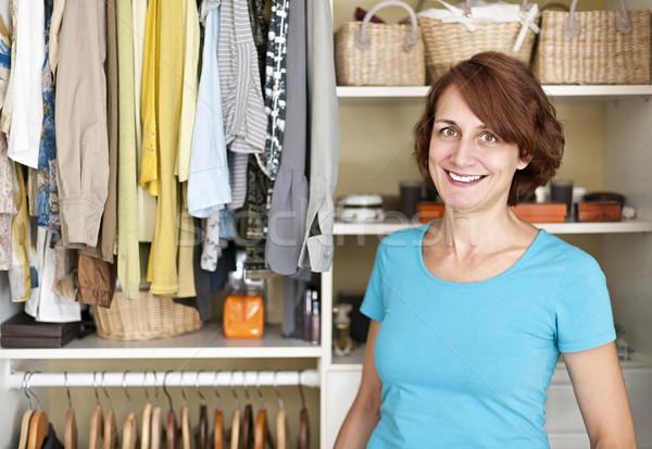 Smiling woman near closet Stock photo © elenaphoto
