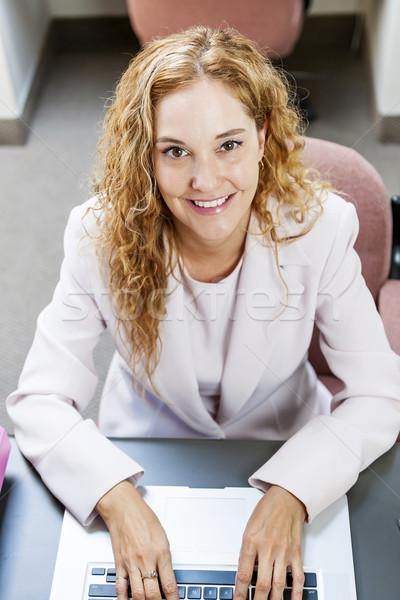 женщину набрав портативного компьютера делопроизводства улыбаясь деловая женщина Сток-фото © elenaphoto