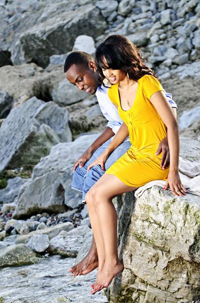 Happy couple sitting at rocky shore Stock photo © elenaphoto