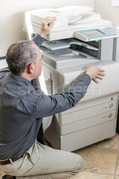 Man opening photocopier in office Stock photo © elenaphoto