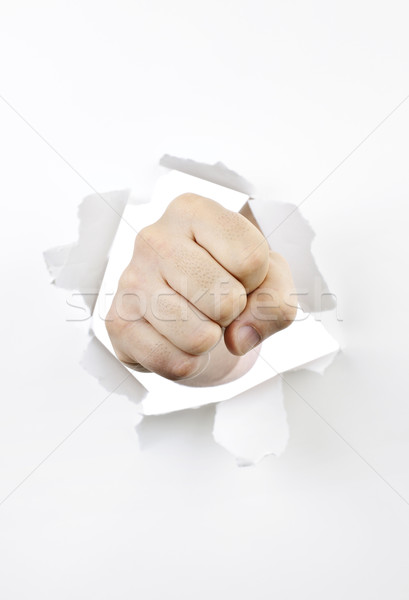 Fist punching through hole in paper Stock photo © elenaphoto