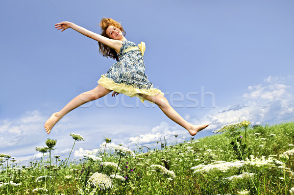 Young girl jumping in meadow Stock photo © elenaphoto