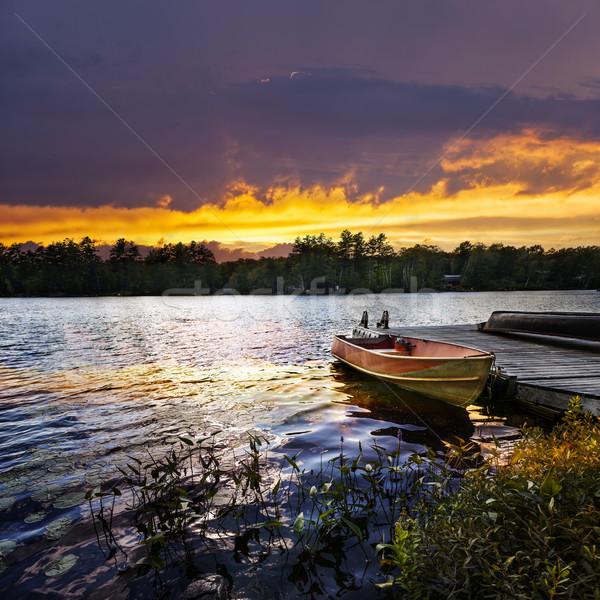 Boat docked on lake at sunset Stock photo © elenaphoto
