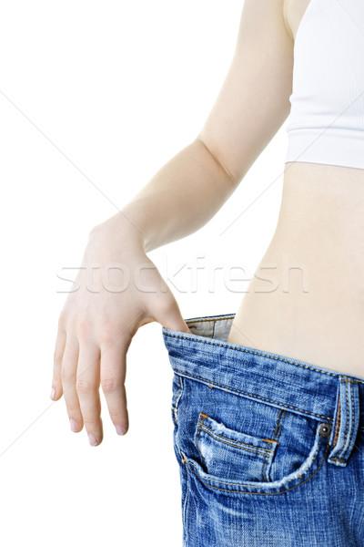 Woman showing weight loss Stock photo © elenaphoto