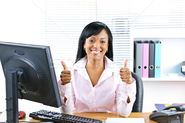 Businesswoman giving thumbs up Stock photo © elenaphoto