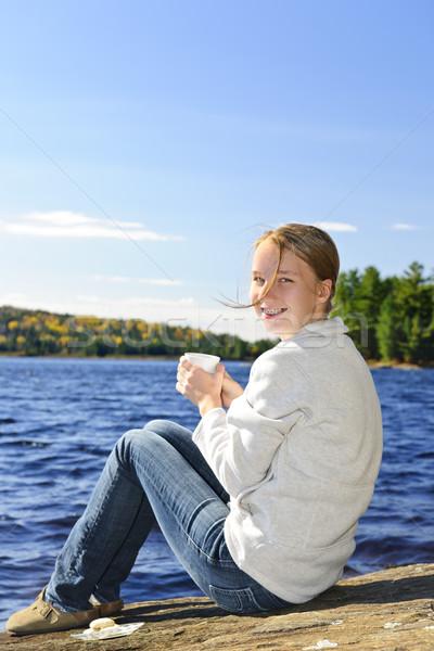 Young woman relaxing at lake shore Stock photo © elenaphoto