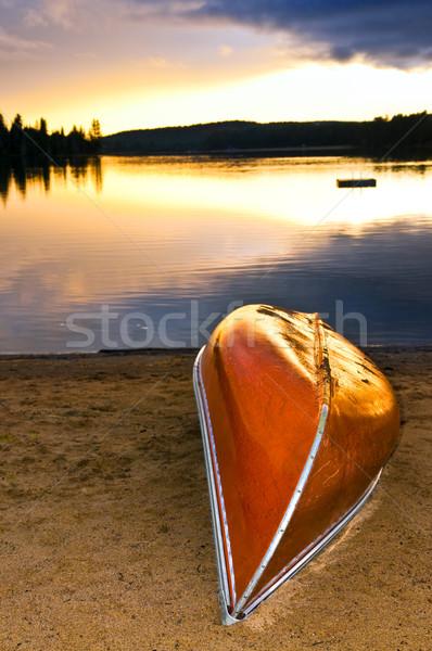 Lago tramonto canoa spiaggia shore nubi Foto d'archivio © elenaphoto