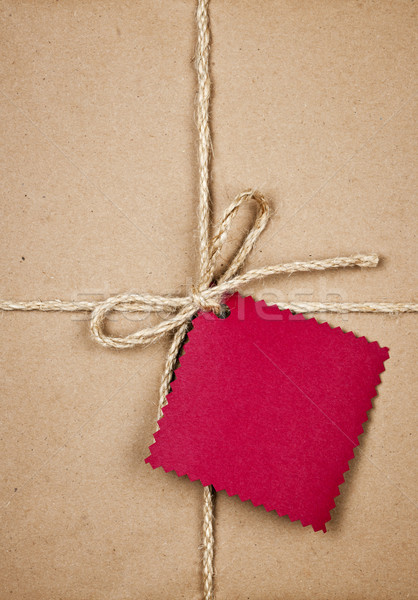 Gift with red tag in brown paper Stock photo © elenaphoto