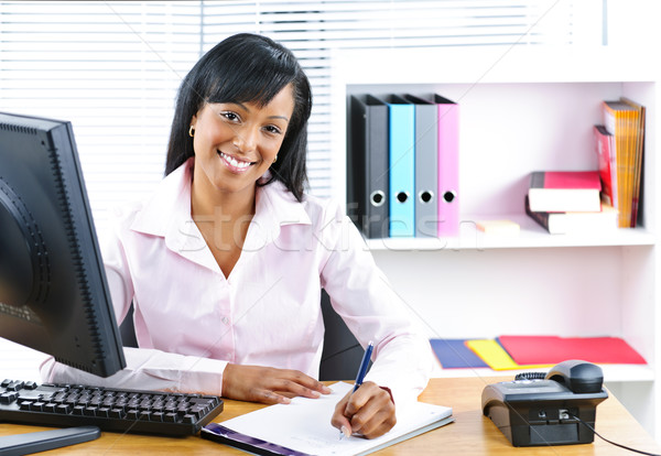 Smiling black businesswoman at desk Stock photo © elenaphoto