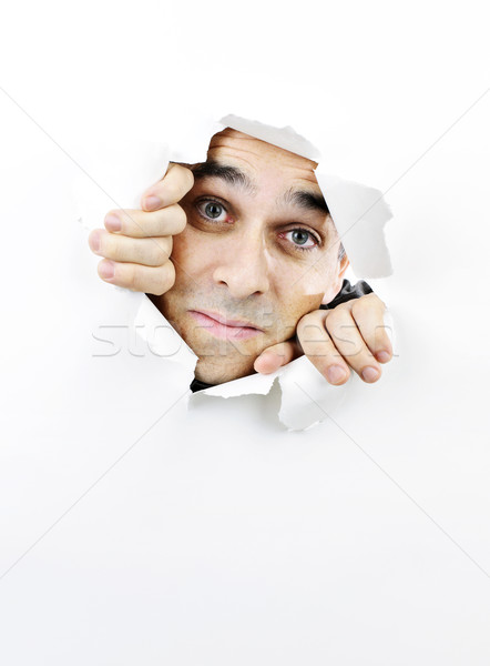 Face looking through hole in paper Stock photo © elenaphoto