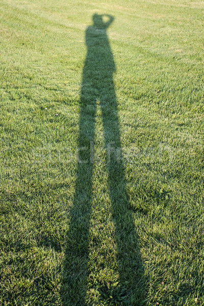 Person casting shadow on grass Stock photo © elenaphoto